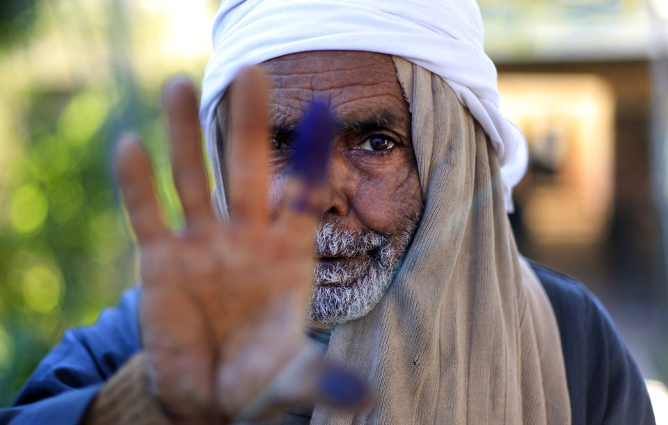 Photo - An Egyptian elderly man shows his inked finger after casting his vote on the second round of a referendum on a disputed constitution drafted by Islamist supporters of President Mohammed Morsi in Fayoum, about 100 kilometers (62 miles) south of Cairo , Egypt, Saturday, Dec. 22, 2012.(AP Photo/Khalil Hamra)