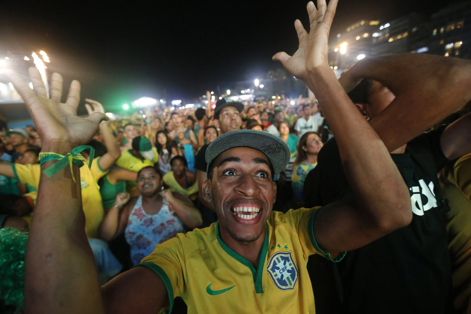 Photo - A Brazil soccer fan celebrates his team's 2-1 victory over Colombia after watching the World Cup quarterfinal game on a live telecast inside the FIFA Fan Fest area on Copacabana beach, in Rio de Janeiro, Brazil, Friday, July 4, 2014. (AP Photo/Silvia Izquierdo)