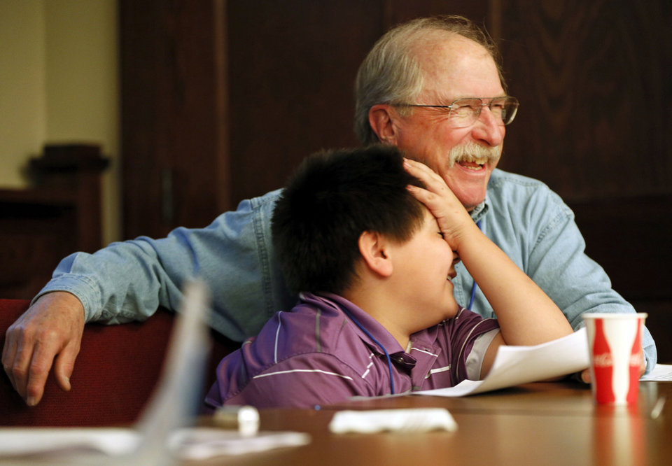 Josh Alvarez, 9, and Randy Dekker, a volunteer from United Methodist Church of the Servant, laugh together during Whiz Kids at Wesley United Methodist, 1401 NW 25. NATE BILLINGS - NATE BILLINGS