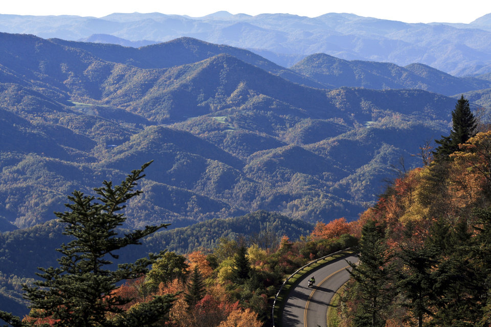 FILE - This Sept. 2007 file photo released by the Explore Asheville shows a motorcyclist on a scenic fall drive along the Blue Ridge Parkway near Asheville, N.C. This gem of a city tucked in the Blue Ridge foothills of western North Carolina attracts artists, musicians, foodies, outdoor enthusiasts and a fair share of modern-day hippies, all lured by the beautiful setting and open-minded vibe.  (AP Photo/Explore Asheville, Valerie L. Jenkins)
