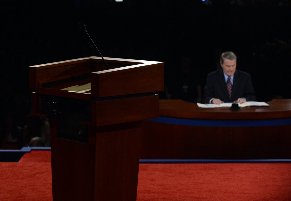Photo -   Moderator Jim Lehrer waits for the start of the first presidential debate at the University of Denver, Wednesday, Oct. 3, 2012, in Denver. (AP Photo/Pool-Michael Reynolds)
