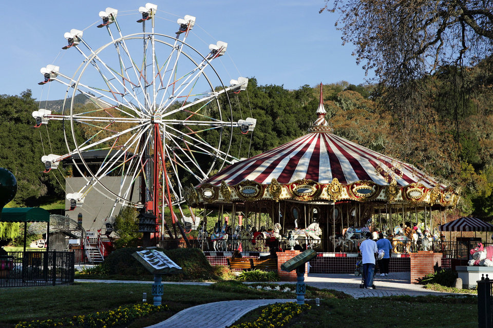 Photo - FILE - This Dec. 17, 2004 file photo shows a carousel, right, and ferris wheel, left, on the property at pop star Michael Jackson's Neverland Ranch home, in Santa Ynez, Calif., where several hundred children were invited to the estate for a holiday celebration. In 2014, Jackson's playtime palace sits empty now. The backyard circus and laughter of children are long gone, but the house and its fanciful memories live on. (AP Photo/Mark J. Terrill, file)