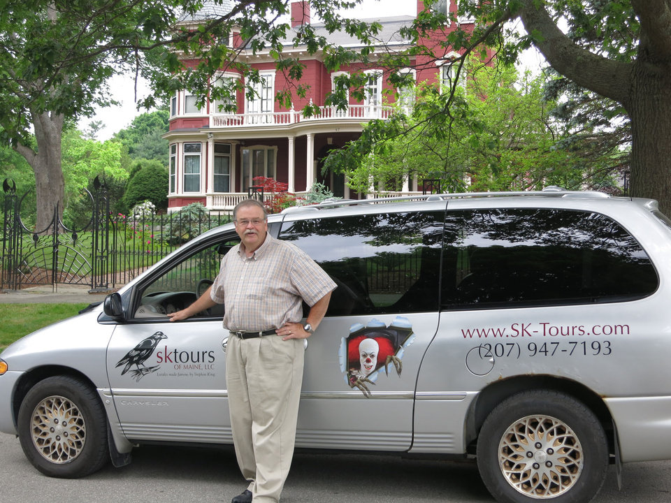 Photo -  Stu Tinker poses with the King Mobile in front of the Stephen King house in Bangor, Maine. Photo courtesy of Jerry Farlow.