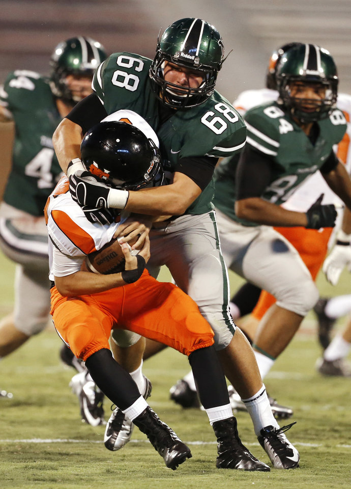 Photo - Norman  North's Evan Coles (68) sacks Norman High School Tiger quarterback Zach Long (16) as the Timberwolves play the Tigers at Gaylord Family/Oklahoma Memorial Stadium in high school football on Thursday, Aug. 30, 2012 in Norman, Okla.  Photo by Steve Sisney, The Oklahoman