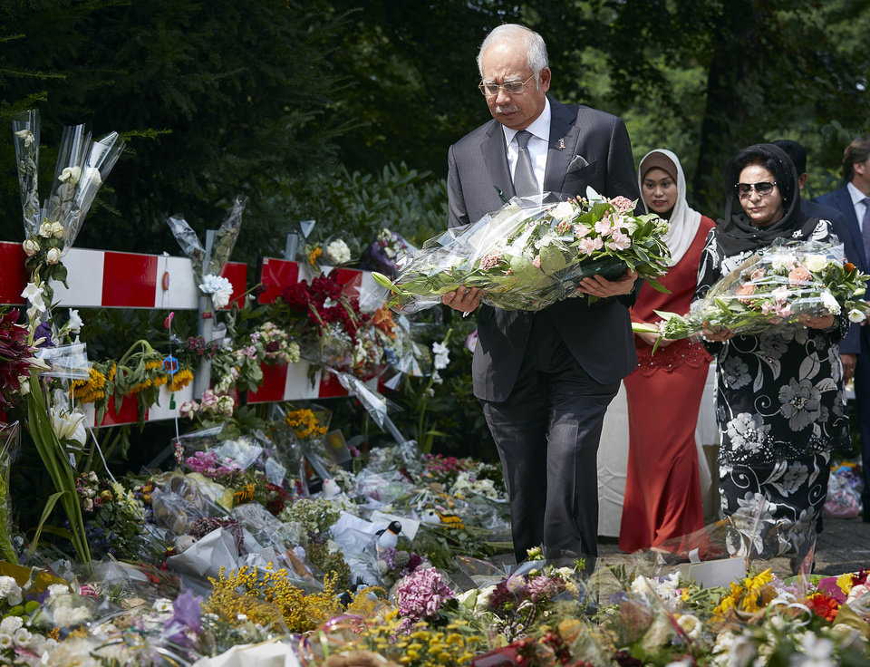 Photo - Malaysian Prime Minister Najib Razak, foreground and his wife Datin Sri Rosmah Mansor, right, lay flowers among other floral tributes, outside a military barracks where forensic experts are working to identify bodies and human remains recovered from the wreckage of Flight 17, in the central city of Hilversum, Netherlands, Thursday, July 31, 2014. Razak is making his first official visit to the Netherlands in the wake of the Malaysia Airlines Flight 17 disaster, in which an ill-fated passenger jet bound from Amsterdam to Kuala Lumpur was shot down in eastern Ukraine on July 17. (AP Photo/Phil Nijhuis)