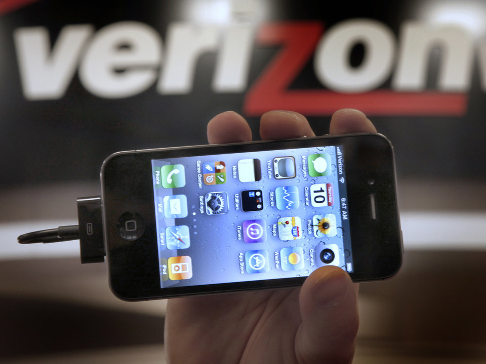Photo - FILE - In this Feb. 10, 2011 file photo, Chris Cioban, manager of the Verizon store in Beachwood, Ohio, holds up an Apple iPhone 4G. Britain's Guardian newspaper says the National Security Agency is currently collecting the telephone records of millions of U.S. customers of Verizon under a secret court order. The newspaper said Wednesday, June 5, 2013 the order was issued in April and was good until July 19. The newspaper said the order requires Verizon on an