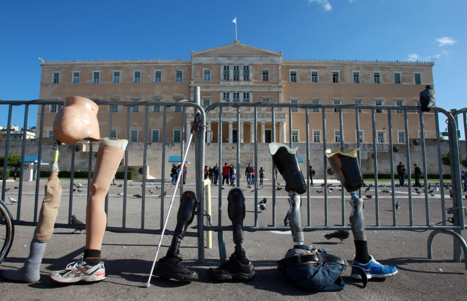 Disabled protesters line up prosthetic limbs outside Greece's parliament in Athens, Monday, Dec. 3, 2012. The protest was part of European demonstrations to mark International Day for People with Disabilities on Monday. Greek campaigners say recent austerity cuts have left many disabled Greeks struggling to receive proper care and state support. (AP Photo/Thanassis Stavrakis)