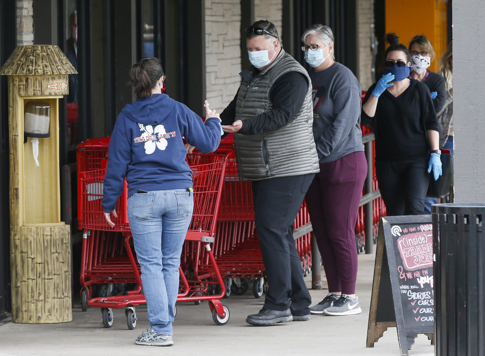 Photo - An employee offers hand sanitizer to a customer entering Trader Joe's in Nichols Hills, Okla., Monday, April 13, 2020. [Nate Billings/The Oklahoman]