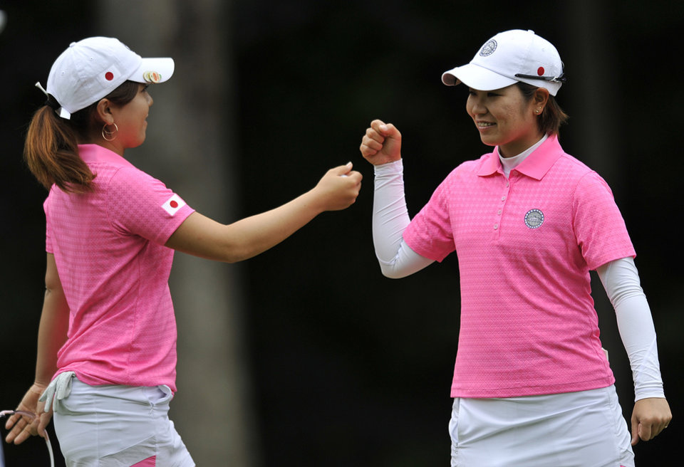 Photo - Mika Miyazato, right, and Mamiko Higa, of Japan, celebrate after putting on the first hole during the first round of the International Crown LPGA golf tournament Thursday, July 24, 2014, in Baltimore.(AP Photo/Gail Burton)