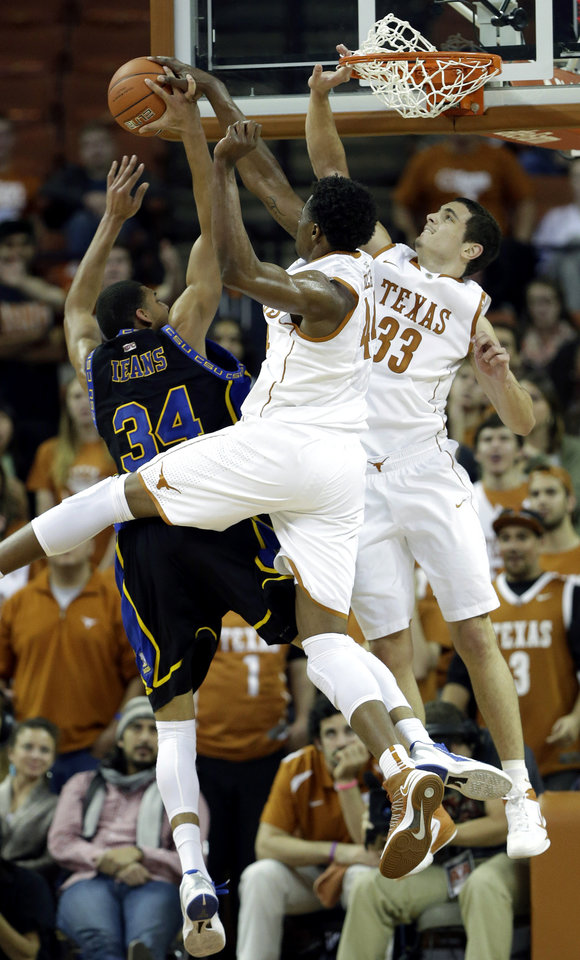 Photo -   Coppin State's Charles Ieans (34) is defended by Texas' Prince Ibeh, center, and Ioannis Papapetrou (33) during the second half of an NCAA college basketball game, Monday, Nov. 12, 2012, in Austin, Texas. Texas won 69-46. (AP Photo/Eric Gay)