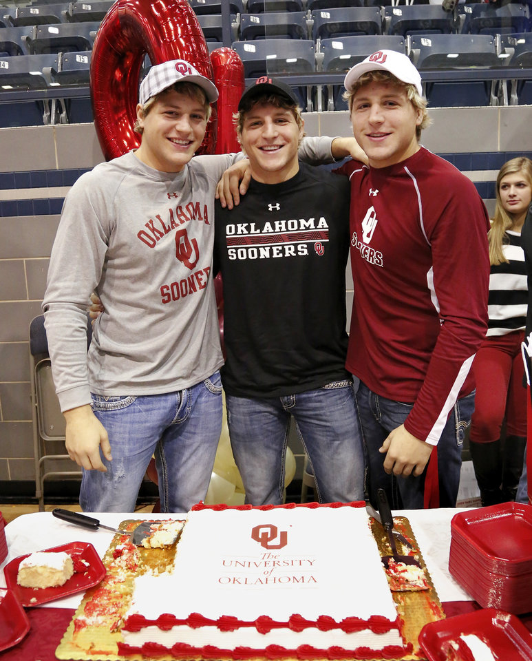 Wrestling brothers, from left, Andrew, Joel and Lance Dixon, pose for a photo after signing with OU. Athletes from Edmond North High School signed national letters of intent with colleges and universities during a ceremony in the school\'s gymnasium Wednesday morning, Nov. 13, 2013. Various sports include golf, softball, wrestling, lacrosse and others. Photo by Jim Beckel, The Oklahoman