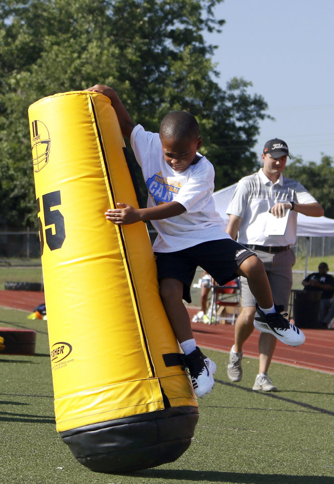 Photo - A camp participant tackles a pop-up dummy at Los Angeles Chargers player Jeff Richards Elite Football Camp at Del City High School in Del City, Oklahoma on July 13, 2019. [Paxson Haws/The Oklahoman]