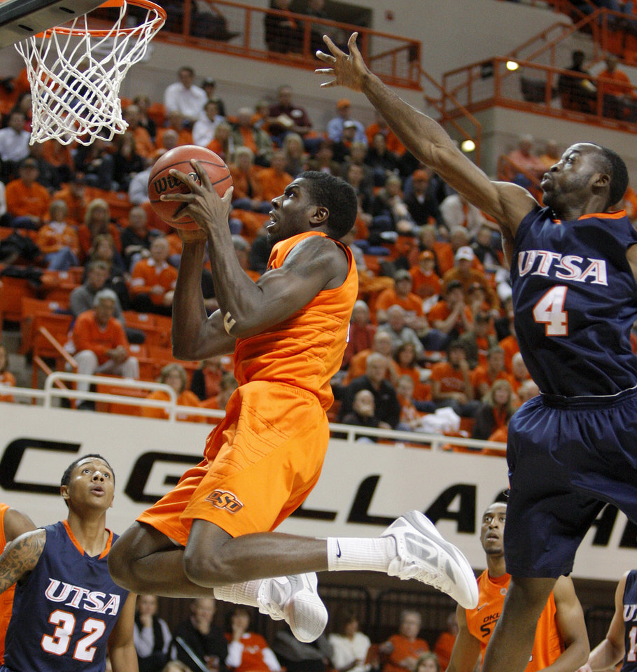 Photo - Oklahoma State's Jean-Paul Olukemi (0) goes to the basket between Texas-San Antonio's Sei Paye (4) and Jordan Sims (32) during an NCAA college basketball game between the Oklahoma State University Cowboys (OSU) and the University of Texas-San Antonio Roadrunners at Gallagher-Iba Arena in Stillwater, Okla., Wednesday, Nov. 16, 2011. Photo by Bryan Terry, The Oklahoman
