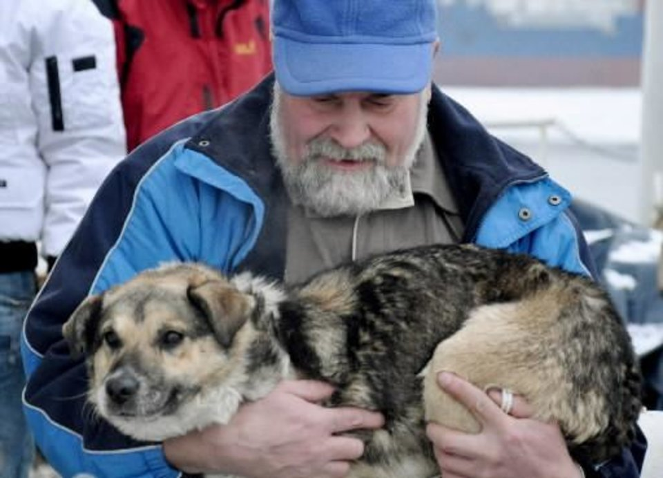 In this photo taken Tuesday, Jan. 26, 2010 and made available Thursday, Jan 28, 2010 Adam Buczynski carries a dog found floating cold and alone on an ice floe 15 miles off the Polish Baltic Sea coast in Gdynia, Poland. Buczynski, a sailor from the ship