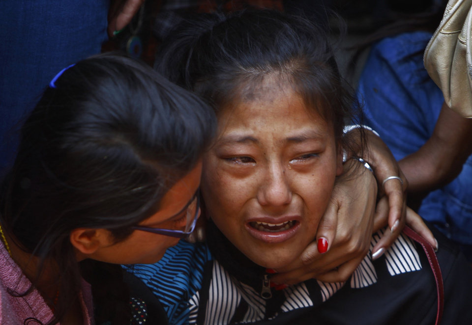 Photo - A relative of one of the Nepalese climbers killed in an avalanche on Mount Everest, cries during the funeral ceremony in Katmandu, Nepal, Monday, April 21, 2014. Buddhist monks cremated the remains of Sherpa guides who were buried in the deadliest avalanche ever recorded on Mount Everest, a disaster that has prompted calls for a climbing boycott by Nepal's ethnic Sherpa community. The avalanche killed at least 13 Sherpas. Three other Sherpas remain missing and are presumed dead. (AP Photo/Niranjan Shrestha)