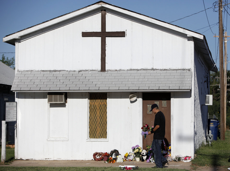 Photo - Peter Belgarde leaves flowers outside the church where the Rev. Carol Daniels was killed in August 2009.  Nearly four years later, the church is closed gone, but the killing remains and open case for  law enforcement. Photo by Sarah Phipps, The Oklahoman  SARAH PHIPPS - THE OKLAHOMAN