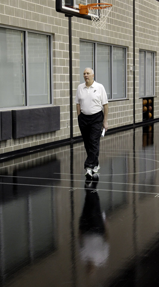Photo -   San Antonio Spurs head basketball coach Gregg Popovich arrives for a news conference where he was named the NBA's Coach of the Year at the team's basketball practice facility, Tuesday, May 1, 2012, in San Antonio. (AP Photo/Eric Gay)