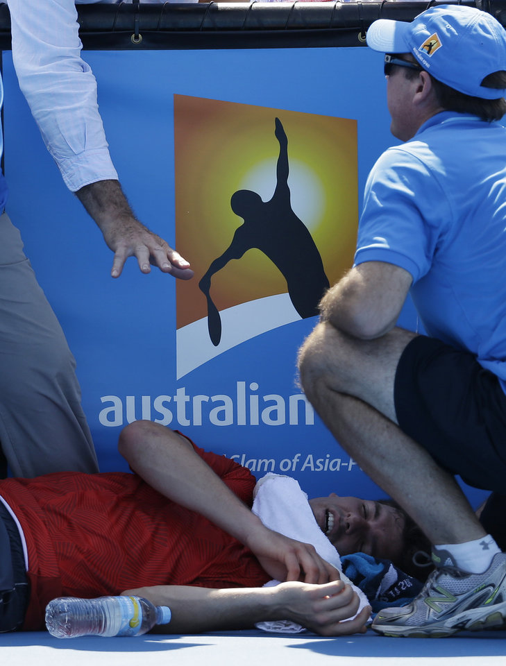 Photo - Frank Dancevic of Canada lies on the court after collapsing during his first round match against Benoit Paire of France as temperatures topped at 43 C (108 F) at the Australian Open tennis championship in Melbourne, Australia, Tuesday, Jan. 14, 2014. (AP Photo/Aijaz Rahi)