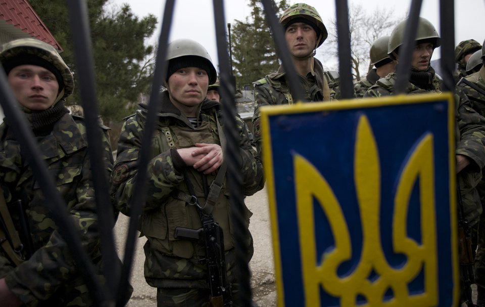 """Photo - FILE - In this Sunday, March 2, 2014 file photo, Ukrainian soldiers guard a gate to their military base in the village of Perevalne, outside Simferopol, Ukraine. On the eve of a referendum vote that has the Black Sea peninsula resting on a razor's edge, those facing the greatest and most fraught uncertainty was are Ukraine's military forces on the peninsula, who have been hemmed in by heavily armed Russian troops and warned by the region's pro-Russian leader that they would be considered """"illegal"""" if they didn't surrender. (AP Photo/Ivan Sekretarev, File)"""