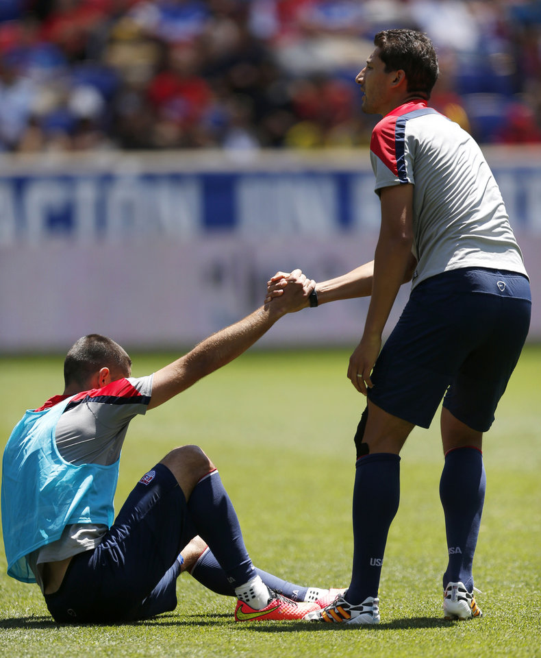 Photo - United States' Clint Dempsey, bottom, is helped up by teammate Omar Gonzalez after a play in which Dempsey fell down and grabbed his ankle during an open practice, Saturday, May 31, 2014, in Harrison, N.J. The United States will face Turkey in an international friendly on June 1. (AP Photo/Julio Cortez)