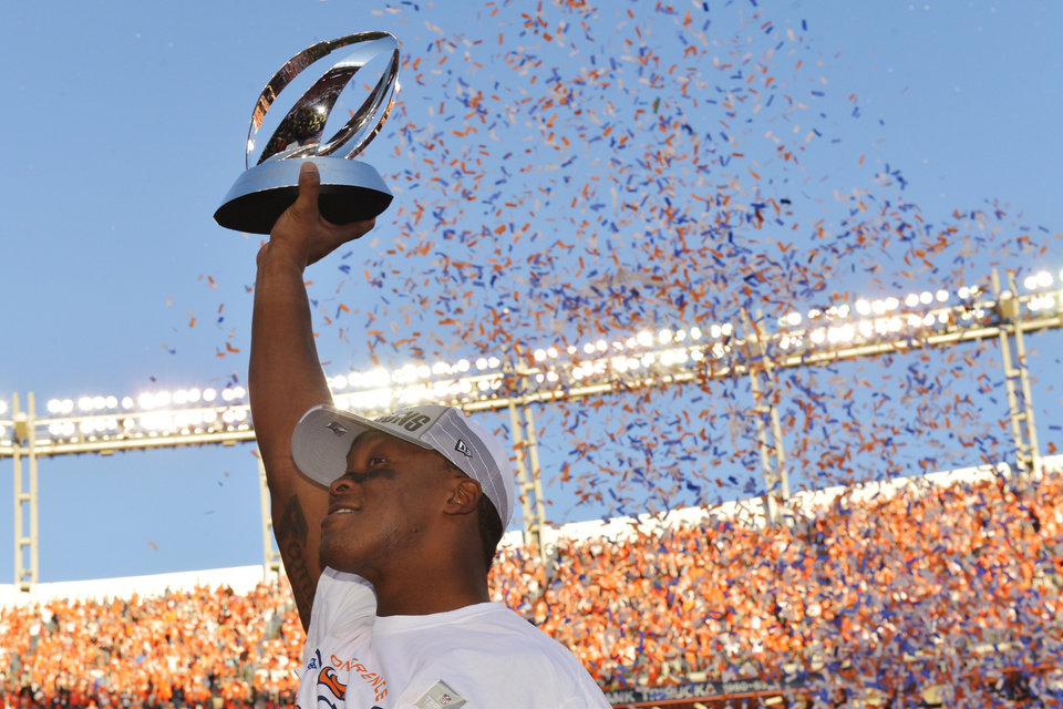 Photo - Denver Broncos wide receiver Demaryius Thomas holds the trophy after the AFC Championship NFL playoff football game against the New England Patriots in Denver, Sunday, Jan. 19, 2014. The Broncos defeated the Patriots 26-16 to advance to the Super Bowl. (AP Photo/Jack Dempsey)