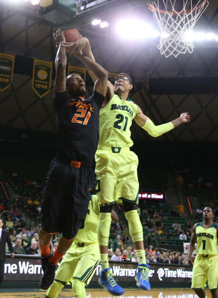 Photo - Oklahoma State center Kamari Murphy (21) is pressured by Baylor center Isaiah Austin (21), right, in the first half of an NCAA college basketball game, Monday, Feb. 17, 2014, in Waco, Texas. (AP Photo/Waco Tribune Herald, Rod Aydelotte)