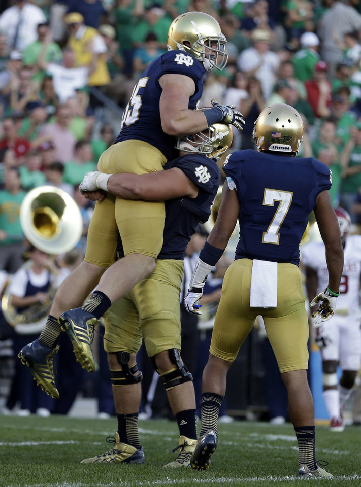 Notre Dame's Troy Niklas (85) celebrates with teammates Nick Martin and TJ Jones (7) after scoring on a 30-yard touchdown reception during the second half of an NCAA college football game against Oklahoma, Saturday, Sept. 28, 2013, in South Bend, Ind. Oklahoma defeated Notre Dame 35-21. (AP Photo/Darron Cummings) ORG XMIT: INDC121
