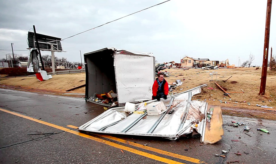 Photo - A worker removes debris from Broadway just north of Waterloo Road in Logan County, Okla., after a storm, Tuesday, Feb. 10, 2009. PHOTO BY BRYAN TERRY, THE OKLAHOMAN