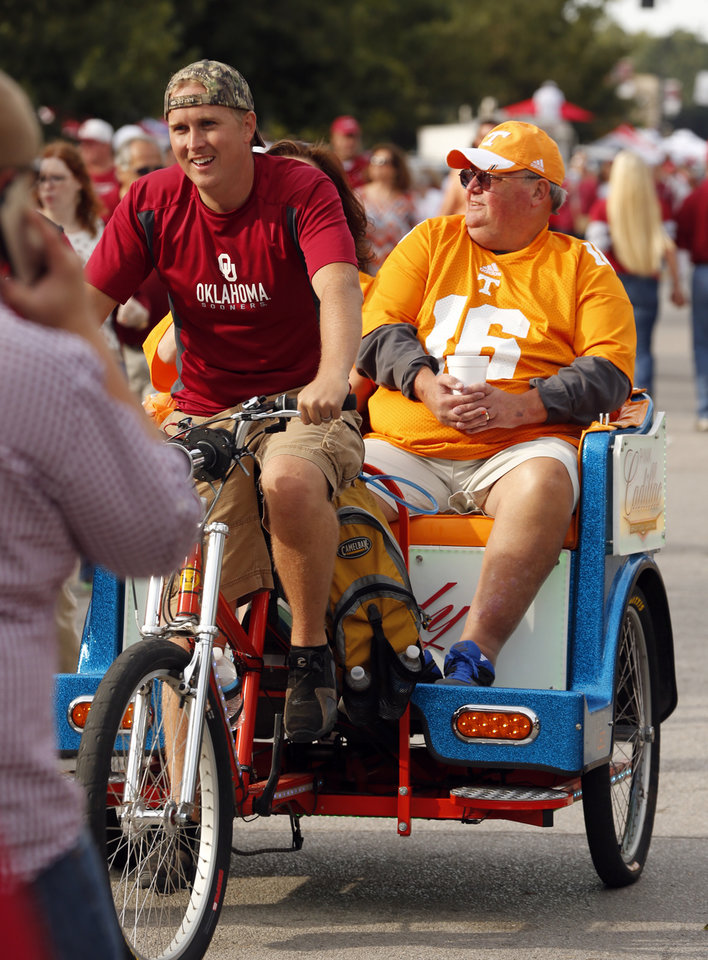 Photo - Tennessee fans ride around campus corner before a college football game between the University of Oklahoma Sooners (OU) and the Tennessee Volunteers at Gaylord Family-Oklahoma Memorial Stadium in Norman, Okla., on Saturday, Sept. 13, 2014. Photo by Steve Sisney, The Oklahoman