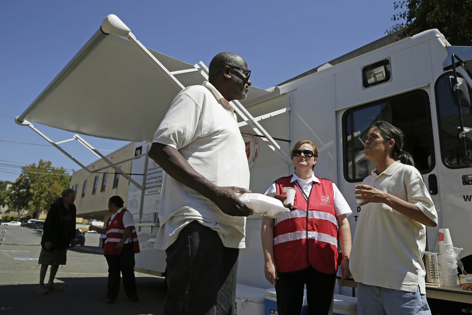 Photo - Salvation Army Capt. Vickie Harvey, second from right, assists people stopping for a boxed lunch or coffee at a disaster services truck outside an earthquake damaged church, Tuesday, Aug. 26, 2014, in Vallejo, Calif. The historic blue-collar town of Vallejo is a short distance but a far cry from the touristy Napa Valley's vineyards and quaint towns, but when Sunday's big earthquake struck, it was not spared. The bayside city that twice was briefly the capital of California sustained more than $5 million in damage and dozens of injuries. It was the latest blow to a town that has weathered years of bankruptcy and is now beset by gangs and crime. (AP Photo/Eric Risberg)