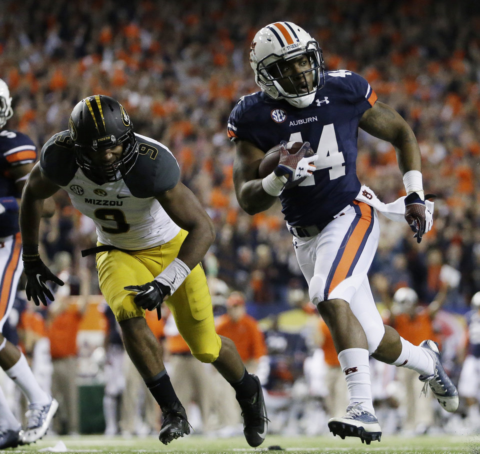 Auburn running back Cameron Artis-Payne (44) runs against Missouri safety Braylon Webb (9) during the second half of the Southeastern Conference NCAA football championship game, Saturday, Dec. 7, 2013, in Atlanta. (AP Photo/David Goldman)