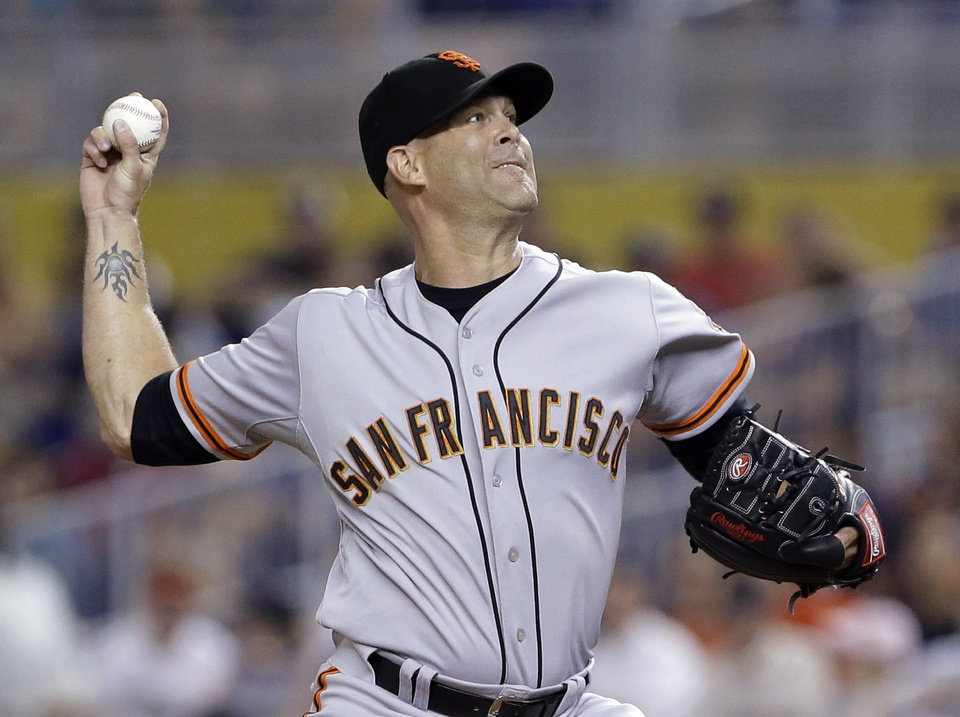 Photo - San Francisco Giants' Tim Hudson delivers a pitch during the first inning of a baseball game against the Miami Marlins, Saturday, July 19, 2014, in Miami. (AP Photo/Wilfredo Lee)