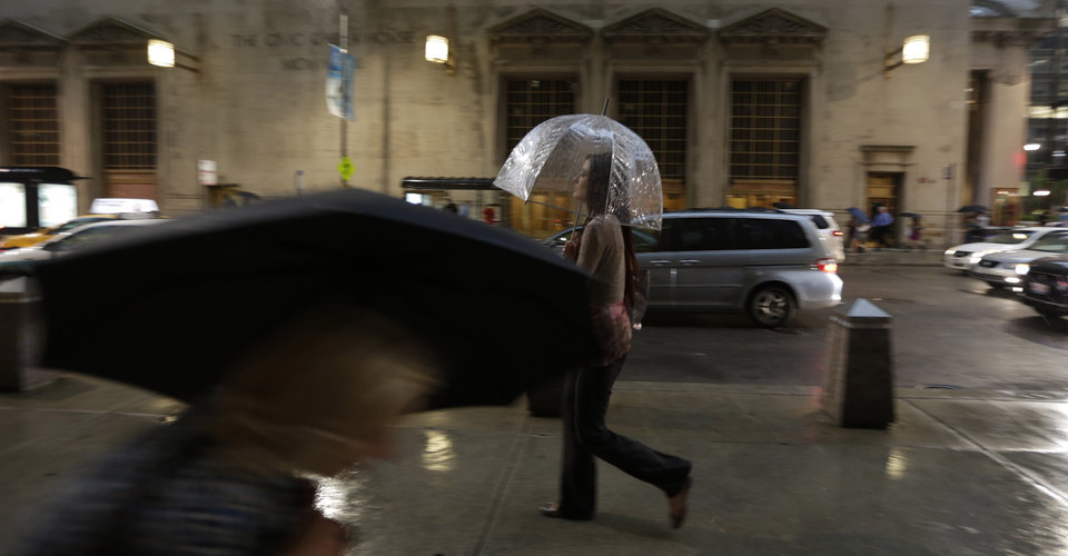 Pedestrian take cover under their umbrellas trying to avoid an unusually massive line of storms packing hail, lightning and tree-toppling winds that have been forecast for evening rush hour, Wednesday, June 12, 2013, in Chicago. (AP Photo/M. Spencer Green)