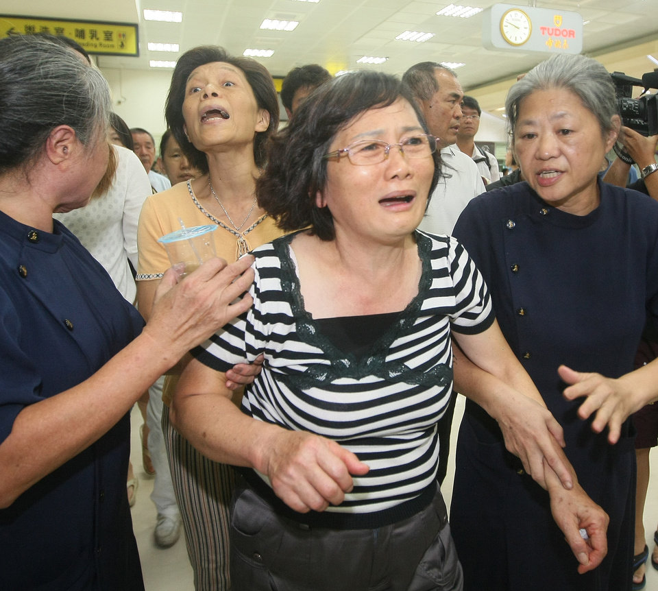 Photo - A relative of a passenger on the Taiwan domestic TransAsia Airways flight GE222 that crashed on the Taiwan island of Penghu, reacts at the flight's departure airport in Kaohsiung, southern Taiwan, late Wednesday, July 23, 2014. Local officials say the domestic airline carrier's plane crashed while attempting to land in rough weather, leaving many people feared dead and some injured. (AP Photo) TAIWAN OUT