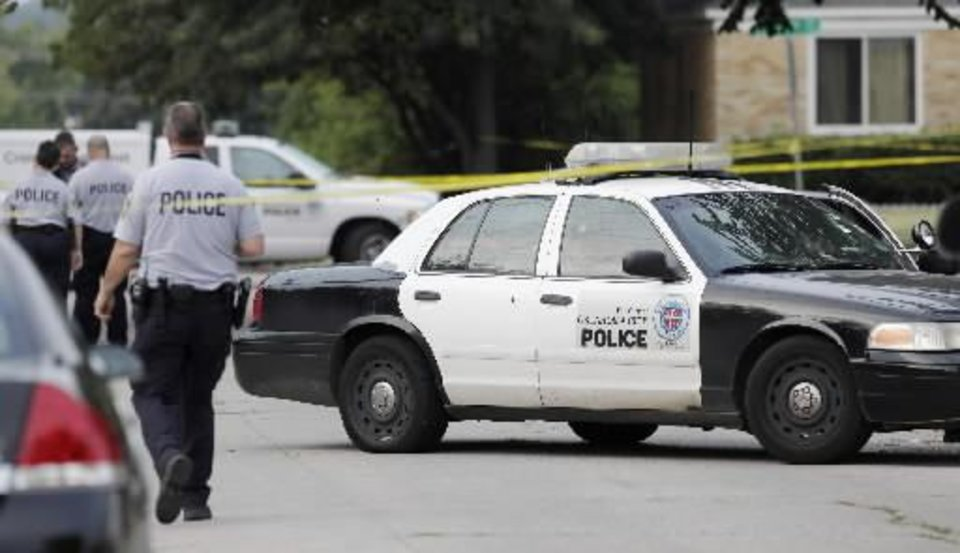 An Oklahoma City police investigator walks past an Oklahoma City police car riddled with bullet holes sitting on Miller Avenue just south of NW 39 Street Monday, August 30 ,2010. A female Oklahoma City police officer was shot in the car. Photo by Paul B. Southerland