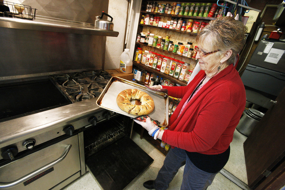 Photo - Donna Bassham removing a  King Cake from the oven that was baked for a fundraiser at Douglas Boulevard United Methodist Church in Midwest City Monday, Jan. 14, 2013.  Photo by Paul B. Southerland, The Oklahoman