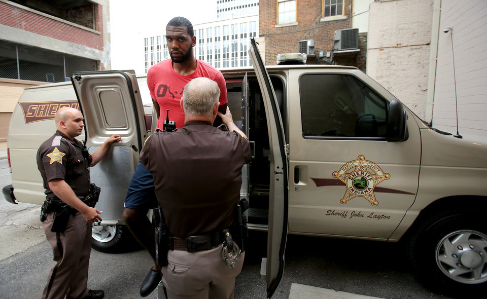 Photo - Greg Oden is escorted into the Marion County Community Corrections building, Thursday, Aug. 7, 2014, in Indianapolis. Police arrested former NBA No. 1 draft pick Greg Oden on battery charges early Thursday, alleging that he punched his ex-girlfriend in the face during a fight at his mother's suburban Indianapolis home. (AP Photo/The Indianapolis Star, Brent Drinkut)  NO SALES
