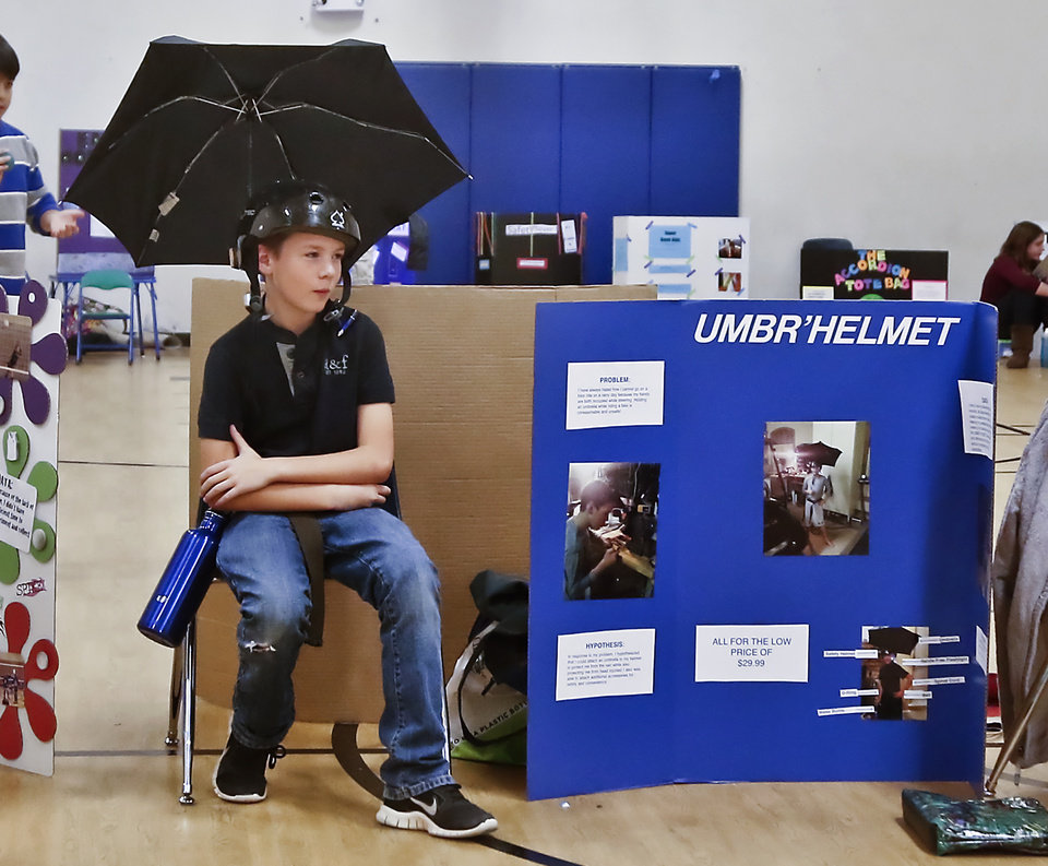A.J. Cox wears his \'Umbr\'Helmet invention during the Deer Creek Middle School science fair on Thursday, March 14, 2013, in Oklahoma City, Okla. Photo by Chris Landsberger, The Oklahoman
