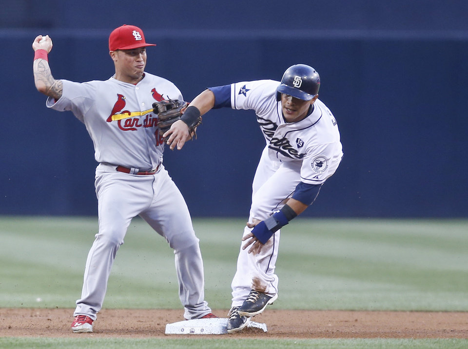 Photo - St. Louis Cardinals second baseman Kolten Wong is unable to get off a decent relay after getting a force out on San Diego Padres' Everth Cabrera at second base in the first inning of a baseball game Wednesday, July 30, 2014, in San Diego.  (AP Photo/Lenny Ignelzi)