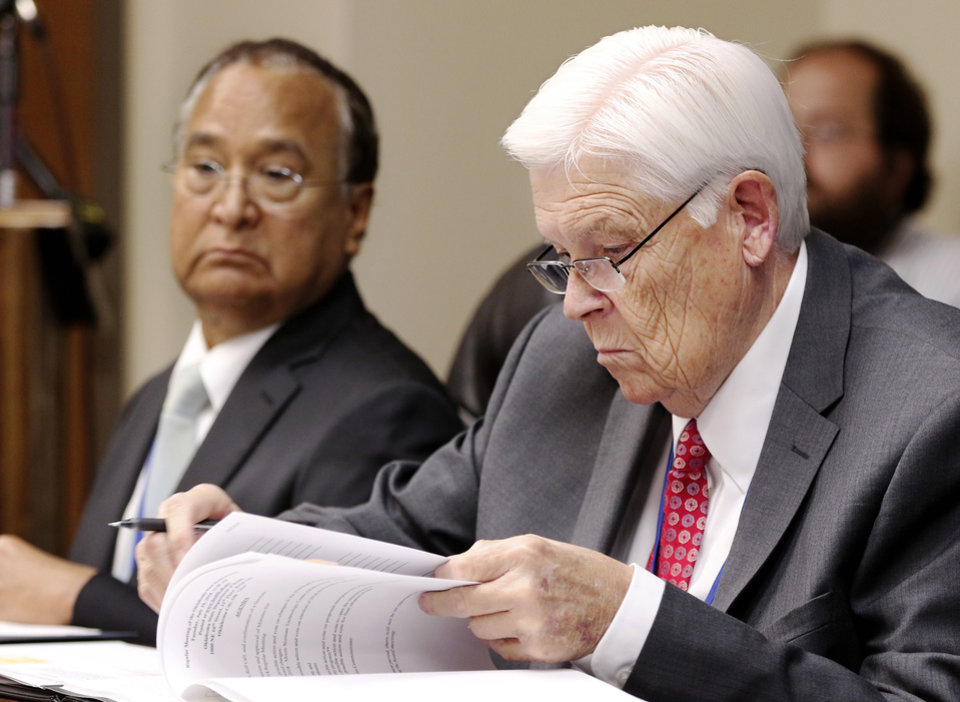 Photo - Ronald Osterhout looks at notes in his binder. At left is Dr. R. Murali Krishna. The Oklahoma State Department of Health voted at their monthly meeting Tuesday morning, July 10, 2018, to ban sales of smokeable forms of medical marijuana and to require dispensaries to hire a pharmacist. The Board of Health voted on 75 pages of rules creating a rough framework for patients, physicians, caretakers and business owners interested in medical marijuana. The ban on sales of leaves and flowers for smoking and the requirement to hire a pharmacist weren't in the draft rules presented to the board, but were a priority of a coalition of medical groups. Julie Ezell, the Health Department's general counsel, presented the rules to a packed board room and to members of the public watching in an overflow room and online. She cautioned board members that the two new rules they added might not be allowed under the state question, inviting a court challenge. Photo by Jim Beckel, The Oklahoman