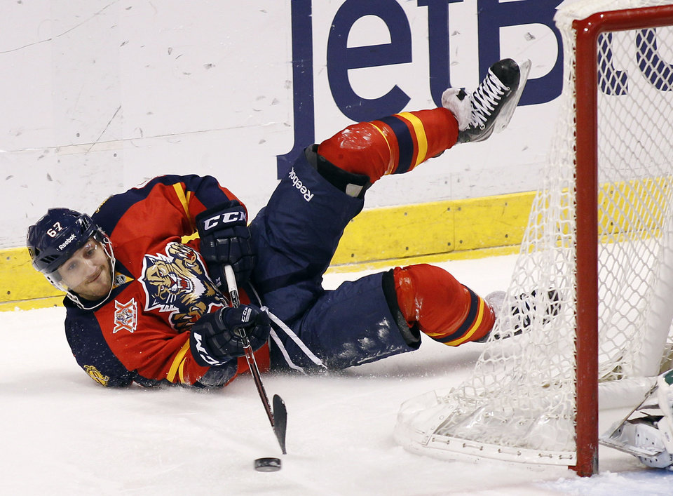 Photo - Florida Panthers center Vincent Trocheck (67) passes the puck as he falls to the ice during the first period of an NHL hockey game against the Dallas Stars in Sunrise, Fla., Sunday, April 6, 2014. (AP Photo/Terry Renna)