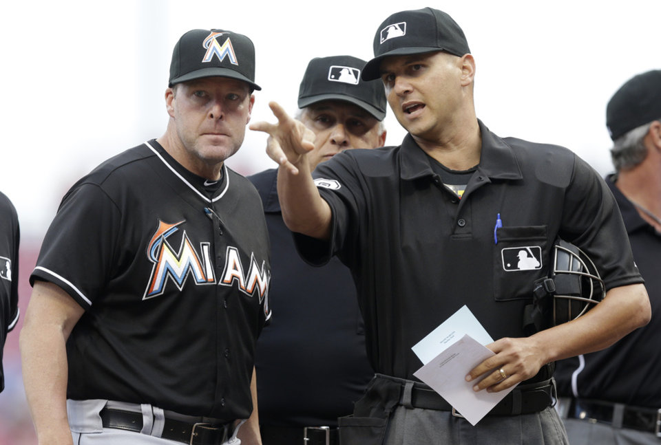 Photo - Miami Marlins manager Mike Redmond, left, goes over the ground rules with home plate umpire Vic Carapazza, right, before a baseball game against the Cincinnati Reds, Friday, Aug. 8, 2014, in Cincinnati. (AP Photo/Al Behrman)