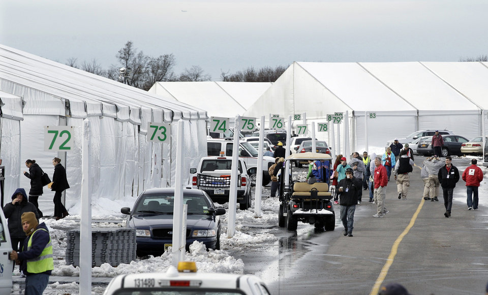 Photo - People walk along rows of large tents Thursday, Nov. 8, 2012, in Oceanport, in Monmouth County, N.J. New Jersey is moving some Superstorm Sandy evacuees from shelters to tent-like housing at Monmouth Park, a racetrack. The facility at Monmouth Park was created to house up to 4,000 out-of-state utility workers and law enforcement officers. State officials say they needed to move the evacuees to the new location temporarily because some buildings used as shelters had to revert to their normal use. (AP Photo/Mel Evans) ORG XMIT: NJME105