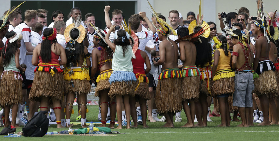 Photo - German's national soccer player Thomas Mueller, center, and his teammates visit with a group of Brazilian Indians who came to watch their training session, near Porto Seguro, Brazil, Monday, June 9, 2014. Germany will play in group G of the 2014 soccer World Cup. (AP Photo/Matthias Schrader)