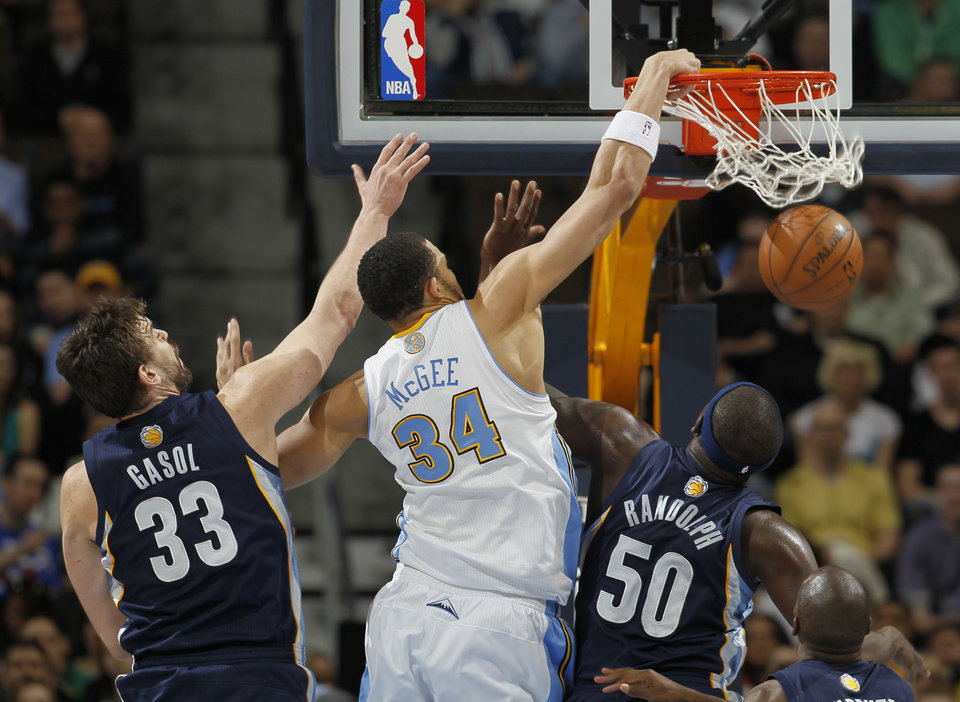 Photo - Denver Nuggets forward JaVale McGee (34) dunks for a basket past Memphis Grizzlies center Marc Gasol (33), of Spain, and forwards Zach Randolph (50) and Quincy Pondexter in the first quarter of an NBA basketball game in Denver, Friday, March 15, 2013. (AP Photo/David Zalubowski)