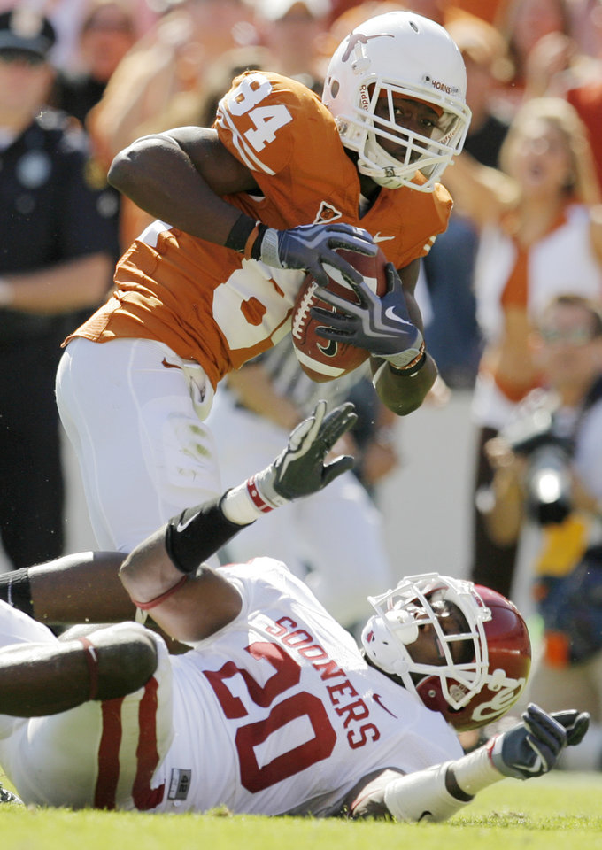 Photo - Marquise Goodwin (84) gets past OU's Quinton Carter (20) on a touchdown reception in the third quarter during the Red River Rivalry college football game between the University of Oklahoma Sooners (OU) and the University of Texas Longhorns (UT) at the Cotton Bowl in Dallas, Texas, Saturday, Oct. 17, 2009. Texas won, 16-13. Photo by Nate Billings, The Oklahoman