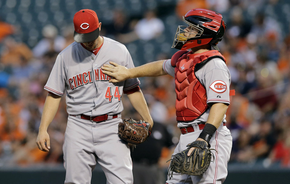 Photo - Cincinnati Reds catcher Tucker Barnhart, right, pats starting pitcher Mike Leake on the chest during a visit to the mound after Leake walked Baltimore Orioles' J.J. Hardy in the first inning of an interleague baseball game, Thursday, Sept. 4, 2014, in Baltimore. Baltimore scored six runs in the first. (AP Photo/Patrick Semansky)