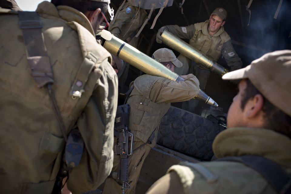 Photo - Israeli soldiers carry shells to their tank following the first death on the Israeli side of the Golan since the Syrian civil war erupted more than three years ago, near the Israeli village of Alonei Habashan, in the area of Tel Hazeka, close to the Quneitra border crossing in the Israeli-controlled Golan Heights, Sunday, June 22, 2014.  A civilian vehicle in the Golan Heights was targeted by forces in neighboring Syria on Sunday in an attack that killed a 15-year-old boy and prompted Israeli tanks to retaliate by firing on Syrian government targets, the Israeli military said. (AP Photo/Oded Balilty)