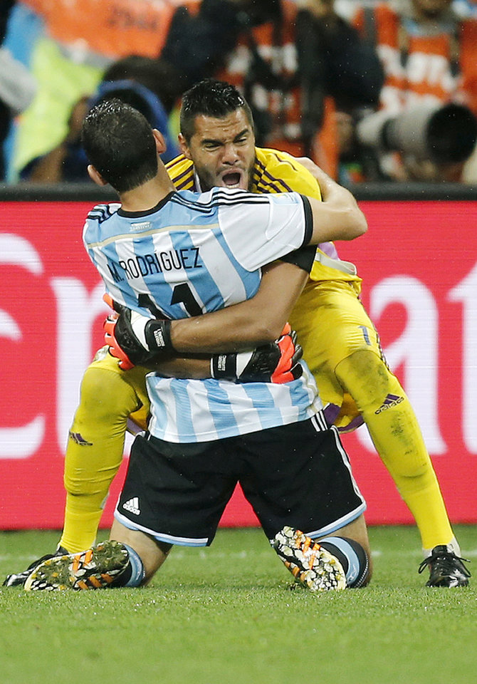 Photo - Argentina's Maxi Rodriguez, front, celebrates with goalkeeper Sergio Romero after scoring the decisive goal during the World Cup semifinal soccer match between the Netherlands and Argentina at the Itaquerao Stadium in Sao Paulo, Brazil, Wednesday, July 9, 2014. Argentina beat the Netherlands 4-2 in a penalty shootout to reach the World Cup final. (AP Photo/Frank Augstein)