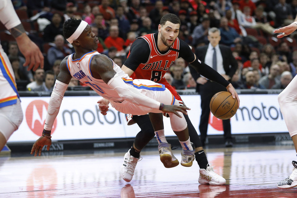 Photo - Oklahoma City Thunder's Dennis Schroeder, left, draws a charge from Chicago Bulls' Zach LaVine during the second half of an NBA basketball game Tuesday, Feb. 25, 2020, in Chicago. The Thunder won 124-122. (AP Photo/Charles Rex Arbogast)